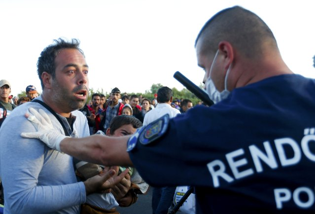 A boy cries as his father speaks to a police officer at a migrants' collection point in the village of Roszke, Hungary, September 7, 2015. (Photo by Laszlo Balogh/Reuters)