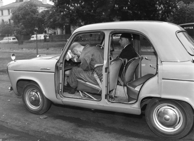 A demonstration of the efficacy of seatbelts in preventing injuries, at the Gloucester Slips in Regent's Park, London, 18th May 1960. An emergency brake causes a dummy passenger with no sash seatbelt to hurtle forward and crack his head on the dashboard. (Photo by William Vanderson/Fox Photos/Hulton Archive)