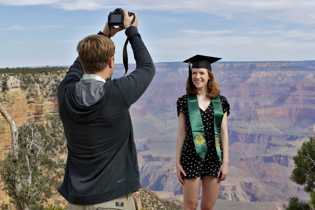 Andrew Fink takes a photo of recent Baylor University graduate Cady Malachowski at the Grand Canyon Friday, May 15, 2020, in Grand Canyon, Ariz. Tourists are once again roaming portions of  Grand Canyon National Park when it partially reopened Friday morning, despite objections that the action could exacerbate the coronavirus pandemic. (Photo by Matt York/AP Photo)
