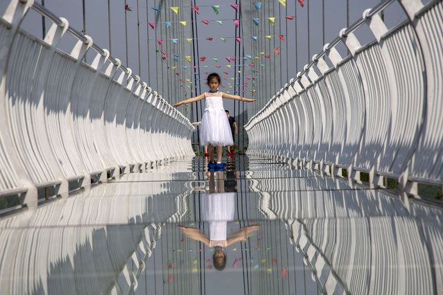 A child stands on a glass-bottomed skywalk on May 21, 2020 in Xiangyang, Hubei Province of China. (Photo by VCG/VCG via Getty Images)