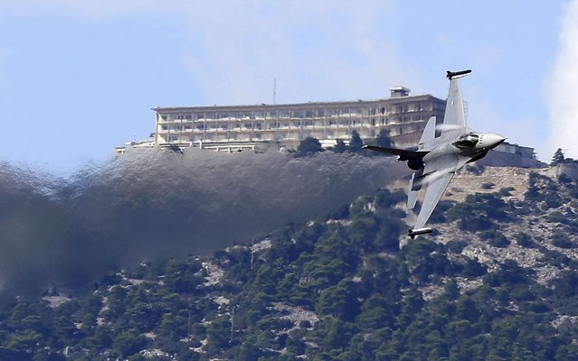 A Dutch F16 fighter jet takes part in an aerobatic display as the pilot flies in front of Casino Mont Parnes atop of the mountain Parnitha during an airshow in northern Athens on Friday, September 26, 2014. The displays launched an annual airshow, known as Athens Flying Week, that will involve planes from several European countries at the weekend at Tatoi airfield. (Photo by Thanassis Stavrakis/AP Photo)