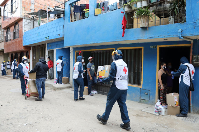 Members of the Colombian Red Cross deliver food aid to the inhabitants of the El Amparo neighborhood in the locality of Kennedy, in Bogota, Colombia, 10 June 2020. A test day for the coronavirus was held on 10 June in the locality of Kennedy in the south of Bogota. The locality remains in total quarantine due to the high number of infections present. (Photo by Carlos Ortega/EPA/EFE/Rex Features/Shutterstock)