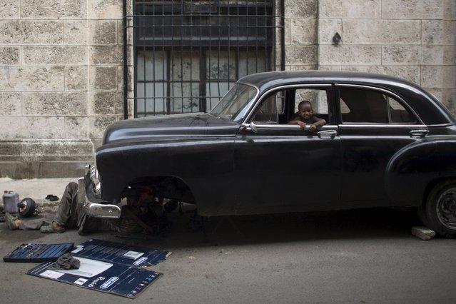 A boy plays inside a vintage car as it is being fixed in downtown Havana, Cuba August 21, 2015. (Photo by Alexandre Meneghini/Reuters)