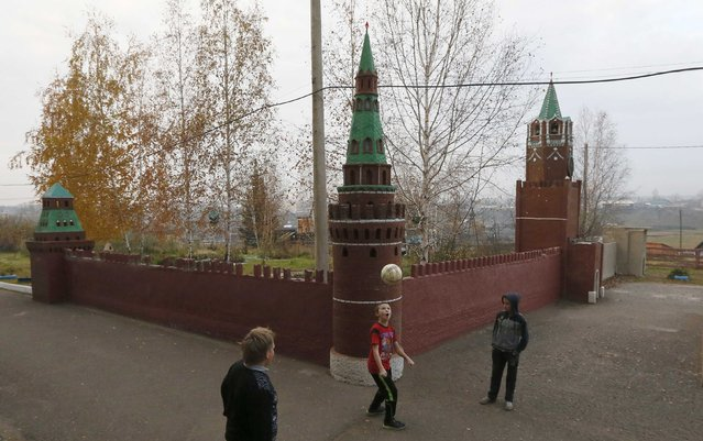 Pupils play with a ball during a break near a replica of three towers and walls of the Moscow's Kremlin located at a school yard in the village of Taseevo, northeast of Krasnoyarsk, Siberia, October 3, 2014. The 1 to 10 scaled replica of the Kremlin, built of self-made bricks, took more then ten years to be built by former local school teacher Vladimir Chernyak and his pupils. The construction is not finished yet, according to school representatives and local residents. Teacher's Day will be marked in Russia on October 5. (Photo by Ilya Naymushin/Reuters)