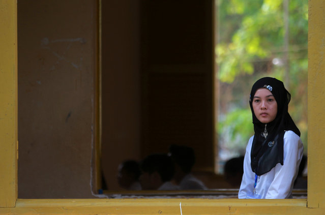 A Muslim invigilator stands near a window as students sit for their final examinations at the Sisowath High School in central Phnom Penh, Cambodia, August 22, 2016. (Photo by Samrang Pring/Reuters)