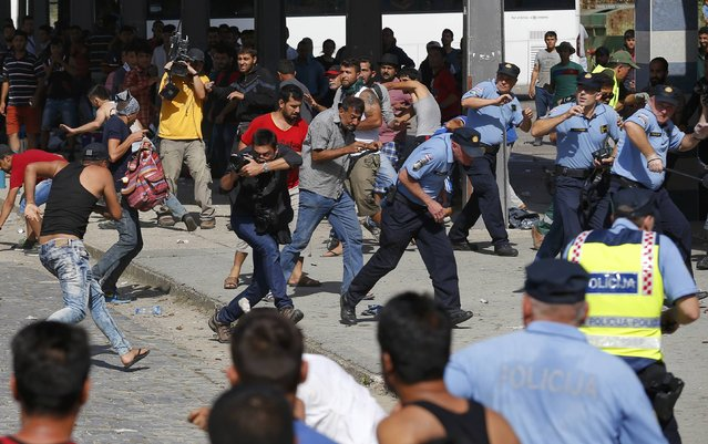 Policemen run as Syrian and Afghan migrants clash at the train station in Beli Manastir, Croatia September 18, 2015. (Photo by Laszlo Balogh/Reuters)