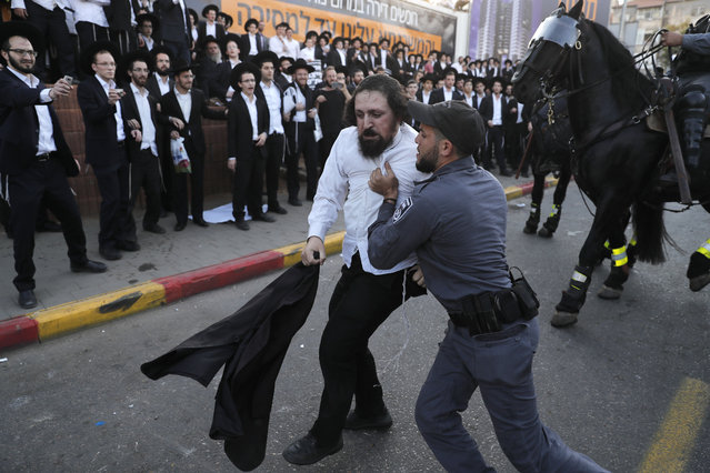 Israeli security forces carry away an Ultra-Orthodox Jewish demonstrator as they disperse a protest against Israeli army conscription in Bnei Brak, a city near Tel Aviv, on November 20, 2017. (Photo by Ahmad Gharabli/AFP Photo)