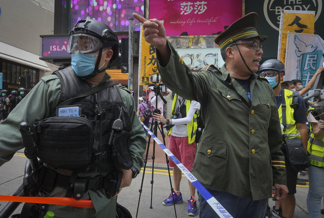 A protester, right, dressed as Chinese police gestures beside police during a protest in Causeway Bay before the annual handover march in Hong Kong, Wednesday, July 1, 2020. Hong Kong marked the 23rd anniversary of its handover to China in 1997, and just one day after China enacted a national security law that cracks down on protests in the territory. (Photo by Vincent Yu/AP Photo)