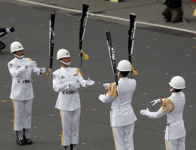 Military honour guards take part during Taiwan's National Day celebrations in front of the presidential office in Taipei October 10, 2014.Taiwan's president on Friday urged China to move toward a more democratic style of development, reiterating his strong support for pro-democracy demonstrations in Chinese-ruled Hong Kong. Ma Ying-jeou used his speech at Taiwan's National Day celebrations to discuss the island's own democratic development in remarks that appeared to show Beijing that Taiwan would never give up its own democracy and rule of law. (Photo by Pichi Chuang/Reuters)