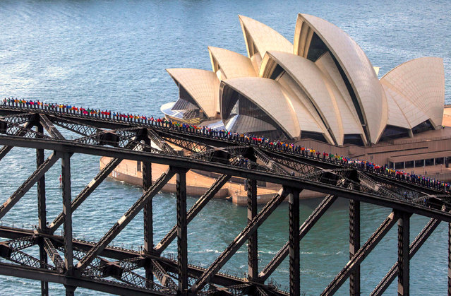A supplied photo shows the Sydney Opera House behind some of the 360 university students from Canada and China as they stand atop of the Sydney Harbour Bridge to set a new record for the most number of people standing on the bridge arc at one time, in Sydney, Australia, November 30, 2017. (Photo by Reuters/Bridgeclimb)