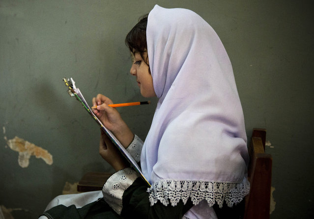 In this Saturday, October 5, 2013 file photo, a young Pakistani girl works on her mid-term papers in a school in Mingora, Swat Valley, Pakistan. (Photo by Anja Niedringhaus/AP Photo)