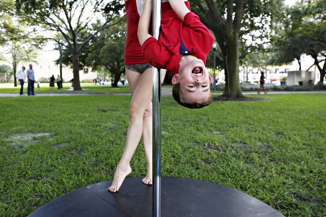 Jeremiah Alvarez, 5, of Brandon, gets some help hanging upside down on a 10-foot fitness pole from Heather Early of St. Petersburg, during a demo day for Impulse Studios in North Sraub Park in St. Petersburg, Fla., Sunday, September 28, 2014. They also had a Lyra and a Fly Gym available for people to try out. (Photo by Melissa Lyttle/AP Photo/Tampa Bay Times)