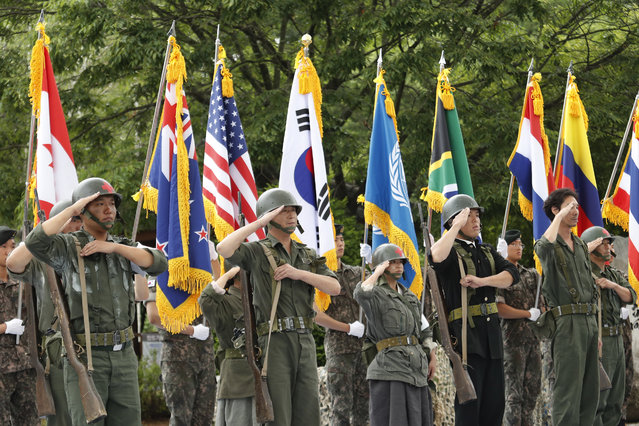 Actors wearing military uniforms with flags of countries which participated in the Korean War salute during a ceremony to mark the 70th anniversary of the outbreak of the Korean War in Cheorwon, near the border with North Korea, South Korea, Thursday, June 25, 2020. The three-year Korean War broke out on June 25, 1950, when Soviet tank-led North Koreans invaded South Korea. (Photo by Ahn Young-joon/AP Photo)