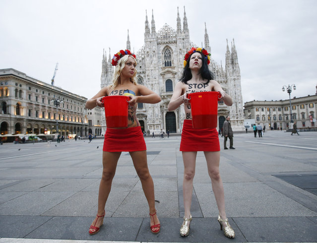 "Inna Shevchenko, left, a member of the Ukrainian feminist protest group FEMEN, and another unidentified activist are about to throw on themselves mock blood as a protest in front of the Duomo gothic cathedral in Milan, Italy, Thursday, October 16, 2014. The 10th Asia-Europe Meeting (ASEM) will take place in Milan, Italy on Thursday 16 and Friday 17 October, 2014, under the theme ""Responsible Partnership for Sustainable Growth and Security"". (Photo by Luca Bruno/AP Photo)"