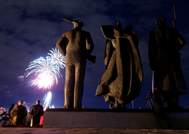 Spectators watch as fireworks explode in the sky in front of the Victory Monument, as part of festive commemorations for the 75th anniversary of the arrival of the first allied Arctic Convoy, Operation Dervish, at the northern port of the Soviet Union during World War Two, in Arkhangelsk, Russia, August 31, 2016. (Photo by Maxim Zmeyev/Reuters)