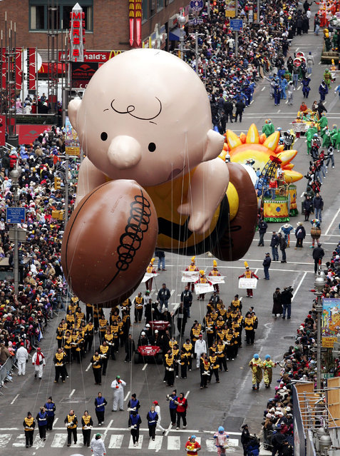 This November 24, 2005 file photo shows a balloon of Peanuts character Charlie Brown chasing a football down Broadway during the Macy's Thanksgiving Day parade in New York. (Photo by Jeff Christensen/AP Photo)