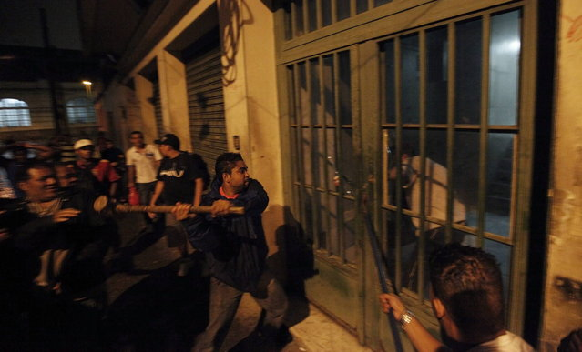Members of Brazil's Movimento dos Sem-Teto (Roofless Movement) break open the front door of a vacant building during the occupation of one of the 11 empty buildings that the movement took over in one night, in the centre of Sao Paulo, October 29, 2012. According to City Hall, there are some 400,000 people in need of stable housing, including the 4,000 families of the Roofless Movement who are squatting in abandoned or vacant buildings that range from apartment blocks to hotels, in Sao Paulo, the largest city in South America. (Photo by Nacho Doce/Reuters)