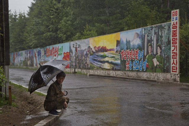 In this June 17, 2014 photo, a North Korean man takes shelter in the rain next to long propaganda billboards in the town of Samjiyon in North Korea's Ryanggang province. (Photo by David Guttenfelder/AP Photo)