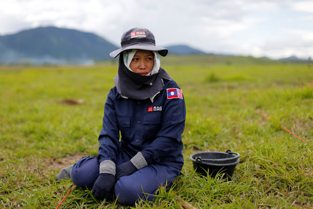 A technician from the NGO Mines Advisory Group (MAG) pauses in a field while searching for unexploded bombs that were dropped by the U.S. Air Force planes during the Vietnam War in Xieng Khouang province, Laos September 2, 2016. (Photo by Jorge Silva/Reuters)
