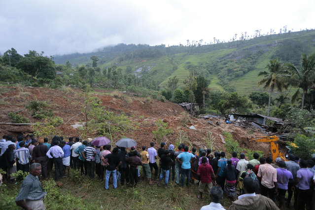 A crowd gathers to watch rescue operation at the site of a mudslide at the Koslanda tea plantation in Badulla district, about 220 kilometers (140 miles) east of Colombo, Wednesday, October 29, 2014. (Photo by Eranga Jayawardena/AP Photo)