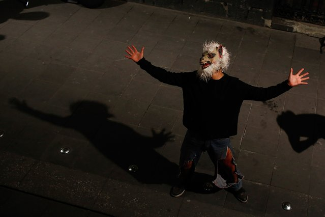 A man wearing a werewolf mask sings in an alley in downtown Mexico City, October 30, 2014. (Photo by Tomas Bravo/Reuters)