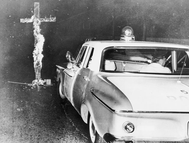 Chicago police move in to knock down a burning cross in front of a home, after an African-American family moved into a previously all white neighborhood, on the 6th consecutive night of disturbances, on August 3, 1963. (Photo by Library of Congress)