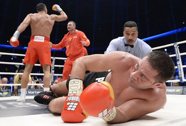 Challenger Bulgarian heavyweight boxer Kubrat Pulev (R) lies in the ring after being knocked down by Ukrainian WBA, WBO, IBO and IBF heavyweight boxing world champion Vladimir Klitschko (L), who celebrates with his brother Vitali (2nd L), as referee Tony Weeks checks on him after their title fight in Hamburg, November 15, 2014. (Photo by Fabian Bimmer/Reuters)