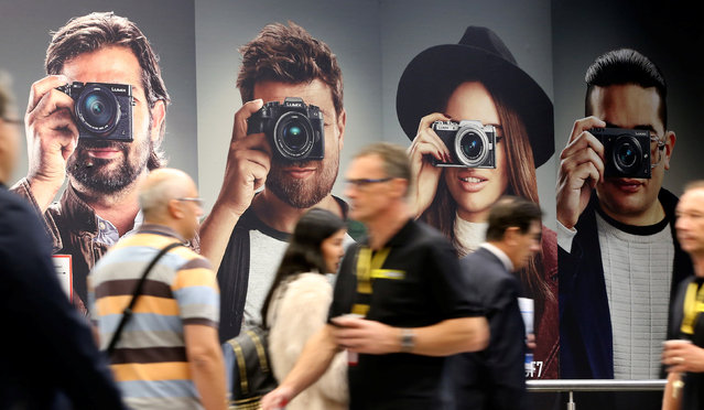 Visitors walk past an advertising poster of Panasonic Lumix digital cameras at the Photokina, the world's largest fair for imaging in Cologne, Germany, September 20, 2016. (Photo by Fabrizio Bensch/Reuters)