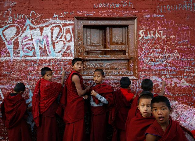 Novice monks write on the wall of a temple during the Shree Panchami festival, dedicated to the goddess of education, Saraswati in Kathmandu, Nepal on January 21, 2018. (Photo by Navesh Chitrakar/Reuters)