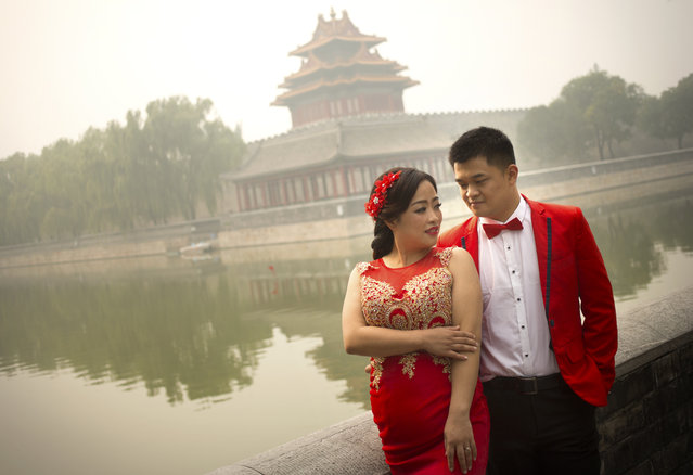 A couple poses for portrait photographs outside of the Forbidden City on a polluted day in Beijing, Wednesday, October 7, 2015. Wednesday is the last day of China's weeklong National Day holiday, traditionally a peak time of the year for tourist travel, but for the second day in a row air quality readings in Chinese capital were at levels considered hazardous by international measuring standards. (Photo by Mark Schiefelbein/AP Photo)