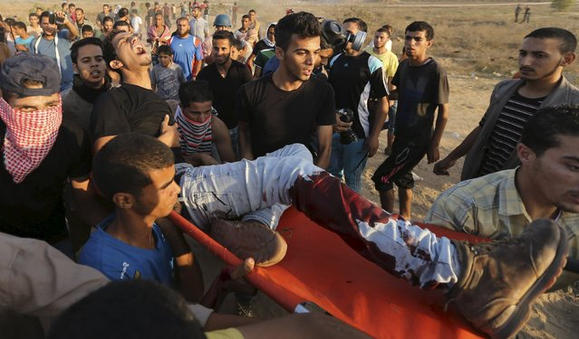 A wounded Palestinian protester is evacuated after he was shot by Israeli troops near the border between Israel and Central Gaza Strip October 17, 2015. At least 40 Palestinians and seven Israelis have died in more than two weeks of unrest, which was in part triggered by Palestinians' anger over what they see as increased Jewish encroachment on Jerusalem's al-Aqsa mosque compound. (Photo by Ibraheem Abu Mustafa/Reuters)