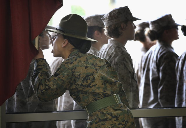 Drill Instructor SSgt. Angela Lopez corrects her female Marine recruits through the window of the chow hall during training in boot camp February 27, 2013 at MCRD Parris Island, South Carolina. Female enlisted Marines have gone through recruit training at the base since 1949. About 11 percent of female recruits who arrive at the boot camp fail to complete the training, which can be physically and mentally demanding. On January 24, 2013 Secretary of Defense Leon Panetta rescinded an order, which had been in place since 1994, that restricted women from being attached to ground combat units. About six percent of enlisted Marines are female. (Photo by Scott Olson/AFP Photo)