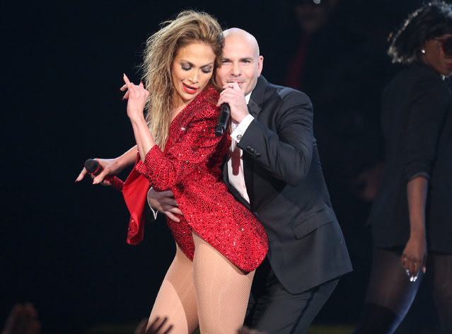 Jennifer Lopez, left, is embraced by Pitbull at the end of her performance at the 42nd annual American Music Awards at Nokia Theatre L.A. Live on Sunday, November 23, 2014, in Los Angeles. (Photo by Matt Sayles/Invision/AP Photo)