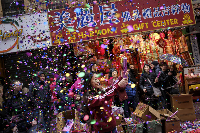 A woman pops confetti during a cultural festival to mark the first day of the Lunar New Year in Chinatown neighborhood in Manhattan, February 16, 2018 in New York City. The 2018 Chinese New Year, which is the year of the dog, begins on Friday and celebrations will last for over two weeks. (Photo by Drew Angerer/Getty Images)