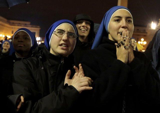Nuns react as black smoke rises from the chimney above the Sistine Chapel, indicating that no decision has been made after the first day of voting for the election of a new pope, in the Vatican City, March 12, 2013.  Roman Catholic Cardinals began their conclave inside the Vatican's Sistine Chapel today to elect a new pope. (Photo by Eric Gaillard/Reuters)