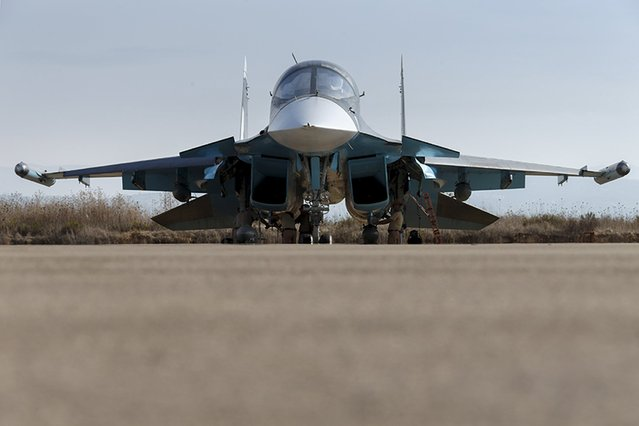 Russian ground staff members work on a Sukhoi Su-34 fighter jet at the Hmeymim air base near Latakia, Syria, in this handout photograph released by Russia's Defence Ministry October 22, 2015. (Photo by Reuters/Ministry of Defence of the Russian Federation)