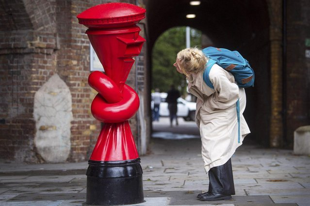"A woman looks at artwork called ""Alphabetti Spaghetti"" by British sculptor Alex Chinneck, one of a series of ""knotted"" postboxes, installed as part of a public art trail for Kensington & Chelsea Art Week on October 3, 2020. (Photo by Victoria Jones/PA Images via Getty Images)"