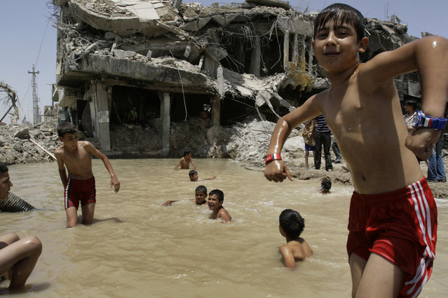 Iraqi boys swim in a pond by a house destroyed in recent fighting in Sadr City in Baghdad, Iraq, on May 20, 2008. (Photo by Karim Kadim/AP Photo/The Atlantic)