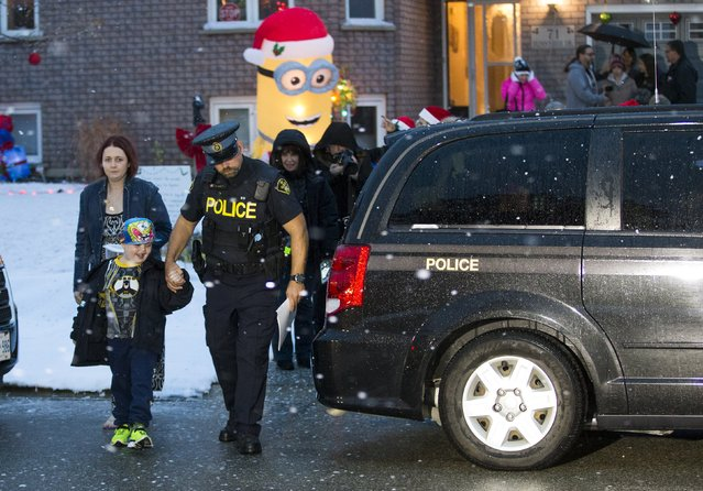Evan Leversage, who is terminally ill with brain cancer, is taken by a police officer as he is going to get a tour of the neighbourhood to see all the Christmas lights with his mother Nicole Wellwood (L) in St. George, Ontario, Canada October 24, 2015. (Photo by Mark Blinch/Reuters)