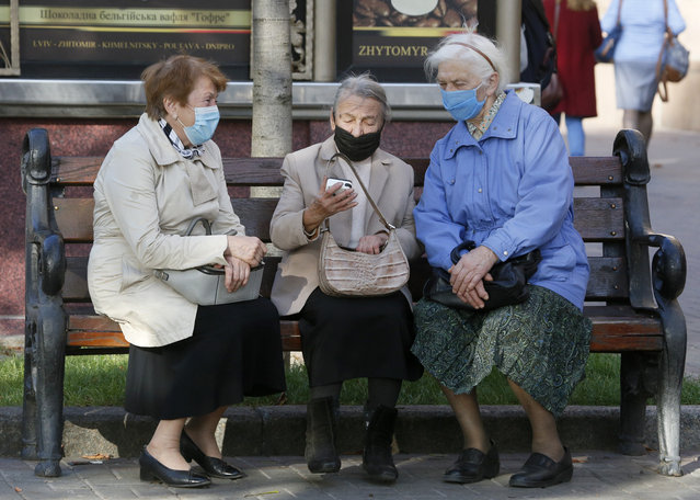 Elderly women wearing face masks to protect against coronavirus look at a phone sitting on a bench in capital Kyiv's main Khreshchatyk Street, Ukraine, Thursday, October 15, 2020. Ukraine has been registering a record number of COVID-19 cases every day. (Photo by Efrem Lukatsky/AP Photo)