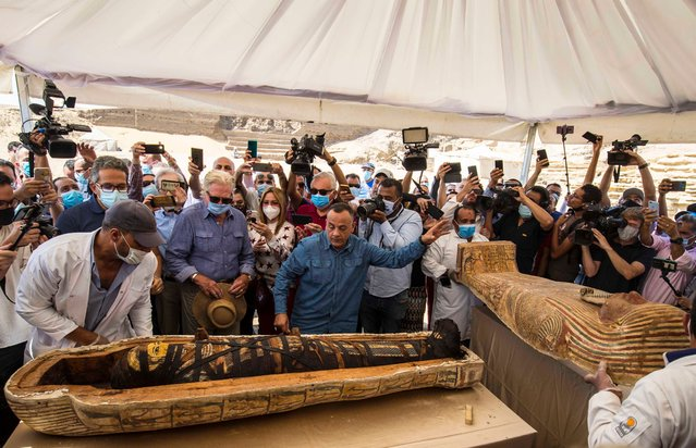 A picture taken on October 3, 2020 shows Egyptian Minister of Tourism and Antiquities Khaled Al-Anani (L), and Mustafa Waziri (R), Secretary General of the Supreme Council of Antiquities, unveil the mummy inside a sarcophagus excavated by the Egyptian archaeological mission working at the Saqqara necropolis, 30 kms south of the capital Cairo, which resulted in the discovery of a deep burial well with more than 59 human coffins closed for more than 2,500 years. They were unearthed south of Cairo in the sprawling burial ground of Saqqara, the necropolis of the ancient Egyptian capital of Memphis, a UNESCO World Heritage site. (Photo by Khaled Desouki/AFP Photo)