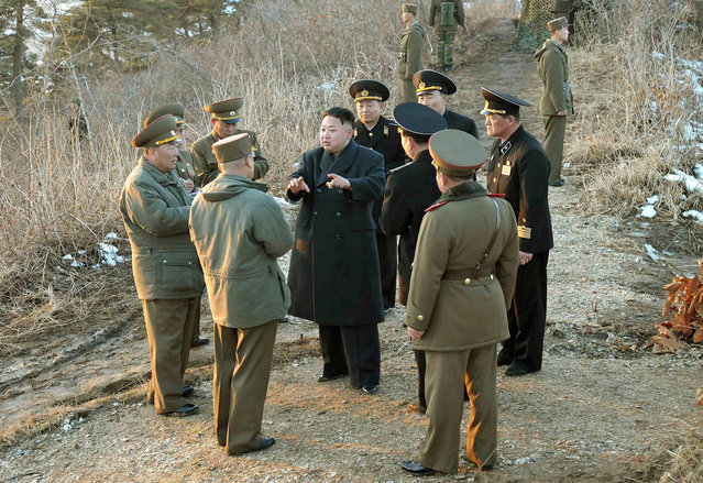 This picture released by North Korea's official Korean Central News Agency on March 26, 2013 and taken on March 25, 2013 shows North Korean leader Kim Jong Un speaking with military officials during his inspection of the landing and anti-landing drills of KPA Large Combined Units 324 and 287 and KPA Navy Combined Unit 597 at an undisclosed location on North Korea's east coast. (Photo by AFP Photo/KCNA via KNS)