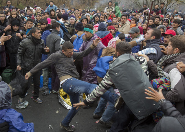 Migrants scuffle as they wait to cross to Austria, in Sentilj, Slovenia, Thursday, October 29, 2015. Asylum-seekers hoping to reach Western Europe turned to crossing Slovenia after Hungary closed its border with Croatia with a barbed-wire fence. (Photo by Darko Bandic/AP Photo)