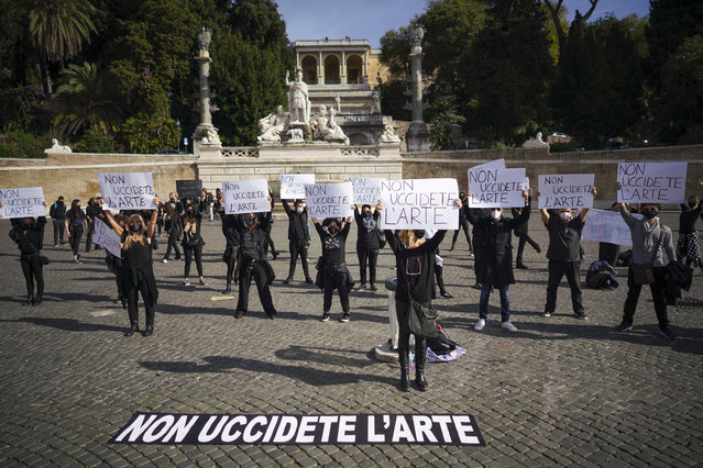 """Dancers and theaters workers hold banners reading in Italian """"don't kill art"""" as they stage a protest against the government restriction measures to curb the spread of COVID-19, closing gyms, cinemas and movie theaters, in Rome, Thursday, October 29, 2020. (Photo by Andrew Medichini/AP Photo)"""