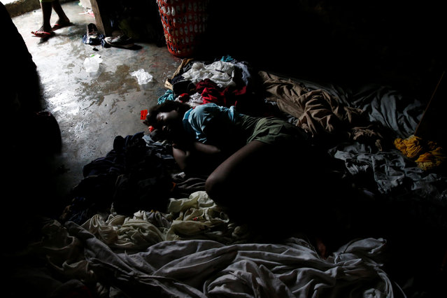 Vlola Joseph sleeps on the floor of her house after Hurricane Matthew passes Cite-Soleil in Port-au-Prince, Haiti, October 5, 2016. (Photo by Carlos Garcia Rawlins/Reuters)