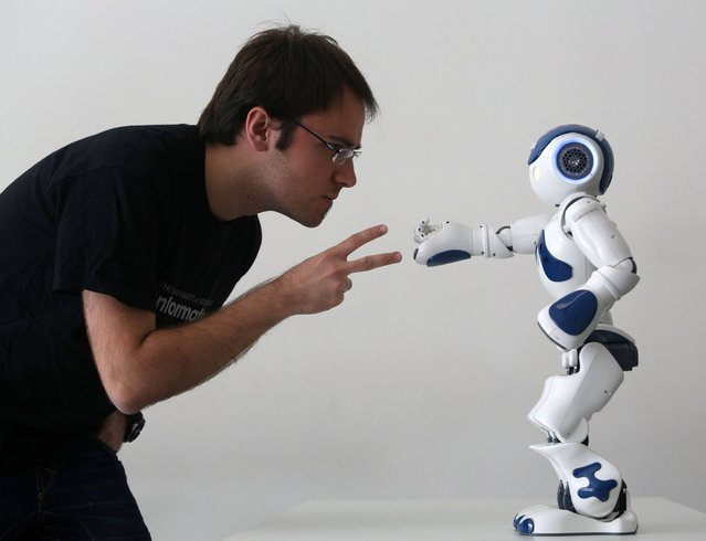 Student Alejadro Bordallo plays rock-scissors-paper with a robot programmed by scientists to use artificial intelligence to learn strategy as they play, part of the Edinburgh International Science festival at the National Museum of Scotland, on April 2, 2013. (Photo by David Cheskin/PA Wire)
