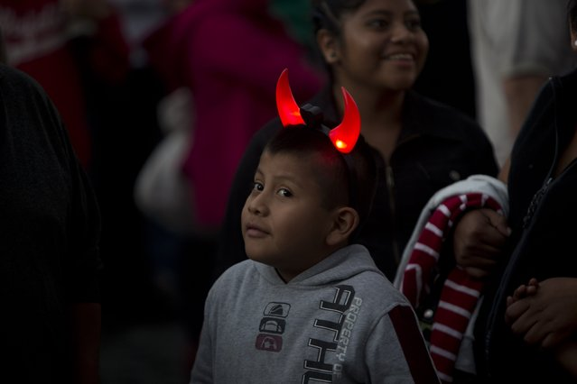 A boy with luminous horns waits for the burning of the devil festival during the Virgin of the Immaculate Conception celebrations in Antigua, Guatemala, Sunday, December 7, 2014. These celebrations mark the beginning of the Christmas Season in Guatemala. (Photo by Moises Castillo/AP Photo)
