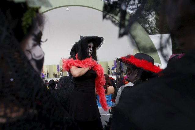 "A woman with her face painted to look like the popular Mexican figure called ""Catrina"", takes part in the annual Catrina Fest in Mexico City November 1, 2015. (Photo by Carlos Jasso/Reuters)"