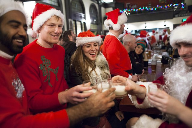 Santarchy participants drink shots at The Pine Box in Seattle, Washington December 13, 2014. (Photo by David Ryder/Reuters)