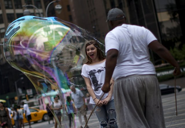 A man circles a tourist in a giant soap bubble at Columbus Circle near Central Park in New York on a warm summer day July 21, 2015. (Photo by Mike Segar/Reuters)